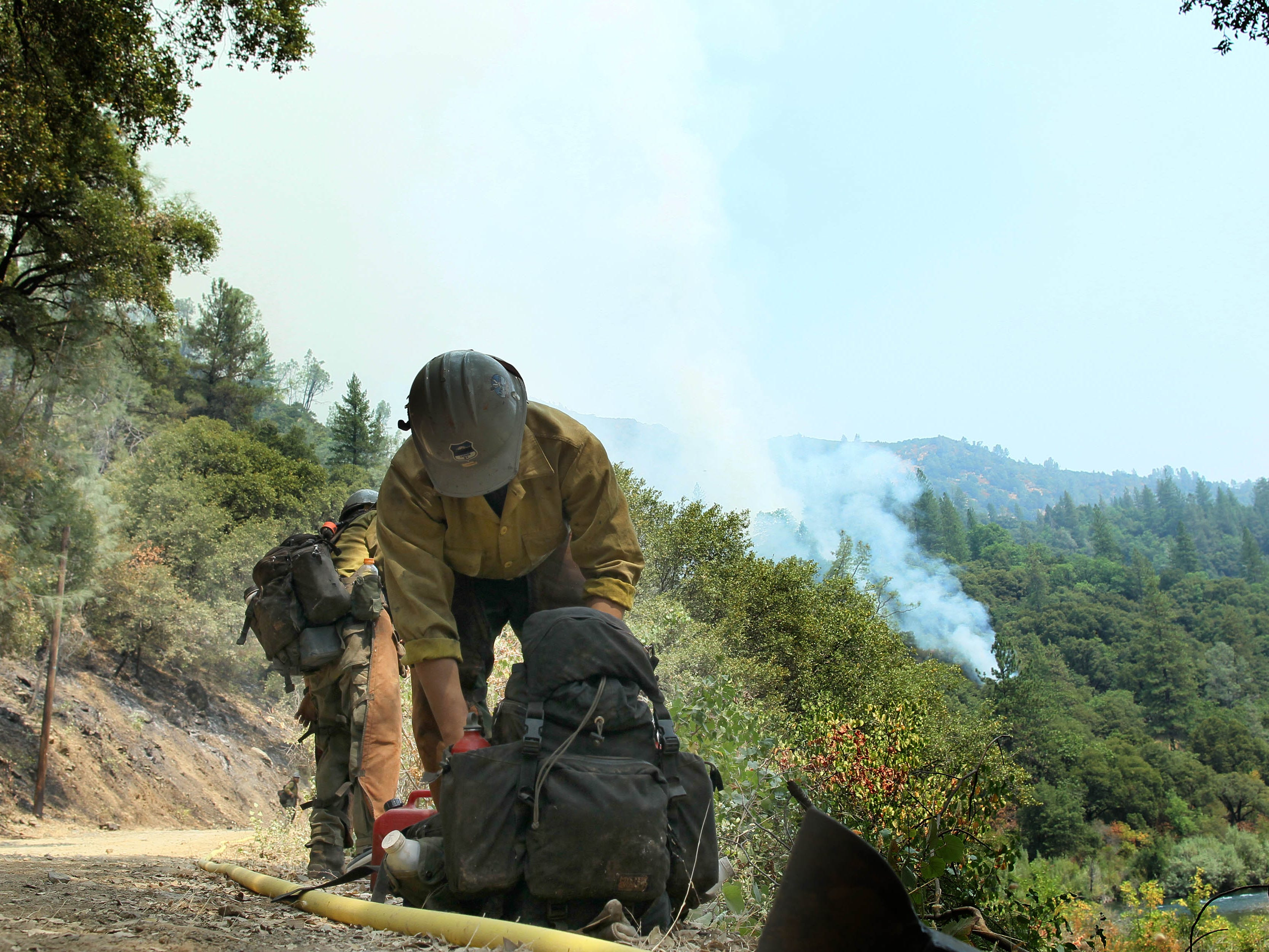 Lee Paoyang of the U.S. Forest Service's hotshot crew Type II Inital Attack, gets his gear ready to move along the McCloud River near Bollibokka at the Hirz Fire on Saturday, Aug. 18, 2018. (Special to the Record Searchlight photo by Hung T. Vu)
