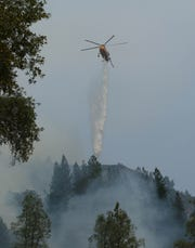 A helicopter drops water on the ridge near Bollibokka Club along the McCloud River on Saturday morning, Aug. 18, 2018. The Hirz Fire is burning in that area. (Special to the Record Searchlight/Hung T. Vu)