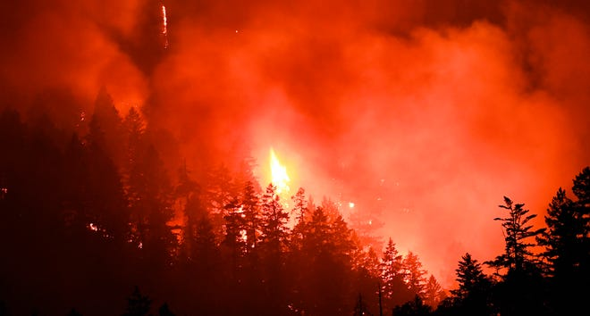 In this Sunday, July 29, 2018 photo, flames from a fire work their way through dense trees near Grants Pass, Ore. People have been forced from their homes as a fire caused by a lightning storm continues to burn near Grants Pass. (Scott Stoddard/The Grants Pass Daily Courier via AP)