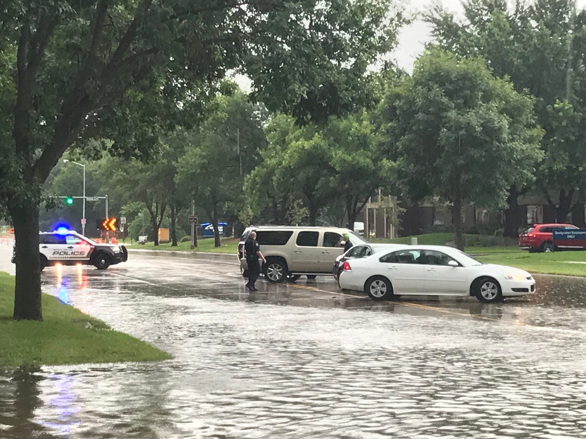 Two cars drive around a police barricade near a flooded road in Sioux Falls.