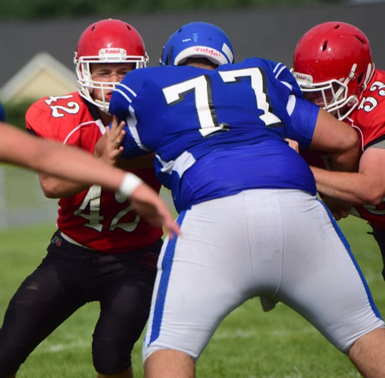 Riverheads' Moose Lee, left, and Zach McCall, double-team Fort Defiance's Caden Morris during their scrimmage at the Riverheads Jamboree on Saturday, Aug. 18, 2018, at Riverheads High School in Greenville, Va.