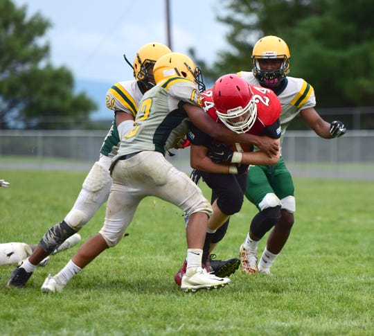 Riverheads running back Jaden Phillips is brought down by three Amelia County defenders during their scrimmage at the Riverheads Jamboree on Saturday, Aug. 18, 2018, at Riverheads High School in Greenville, Va.