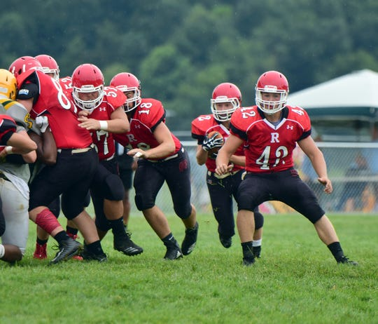 Riverheads running back Devin Morris, center, slips between his line and fullback Moose Lee, right, during the Gladiators' scrimmage against Amelia County at the Riverheads Jamboree on Saturday, Aug. 18, 2018, at Riverheads High School in Greenville, Va.