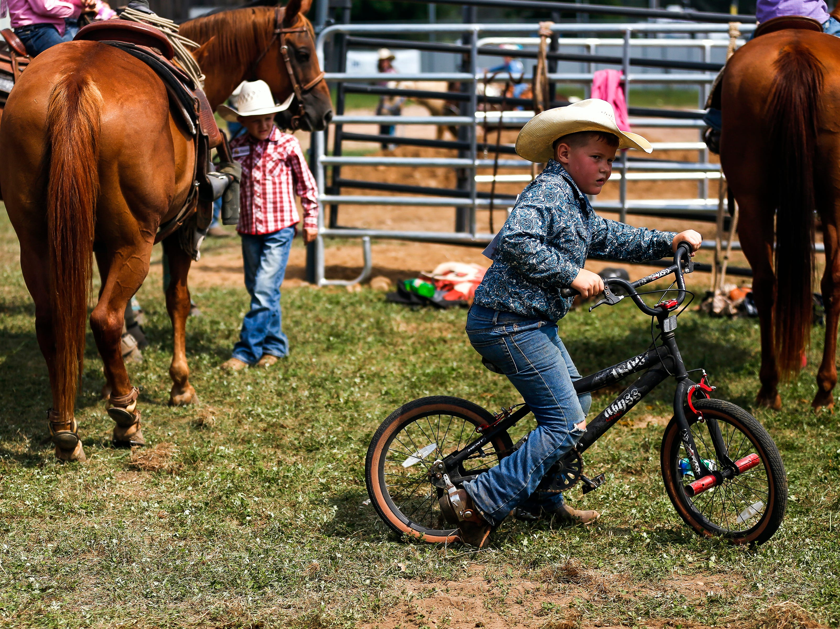 A boy rides a bike through the fairgrounds during the Amherst Little Britches Wisconsin Rodeo in Amherst, Wis., August 17, 2018.