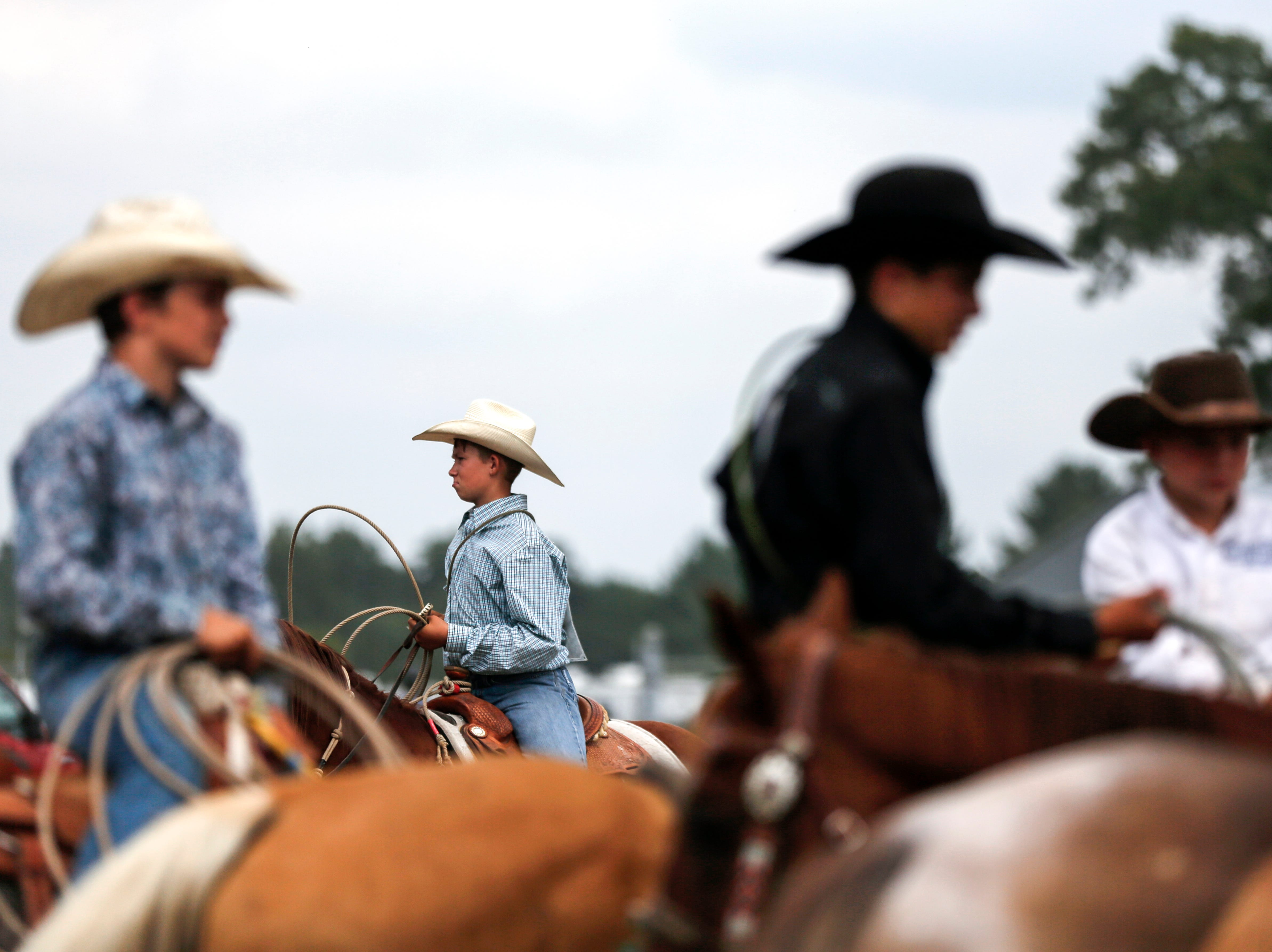 Riders wait for their turn to compete in the calf roping competition during the Amherst Little Britches Wisconsin Rodeo in Amherst, Wis., August 17, 2018.