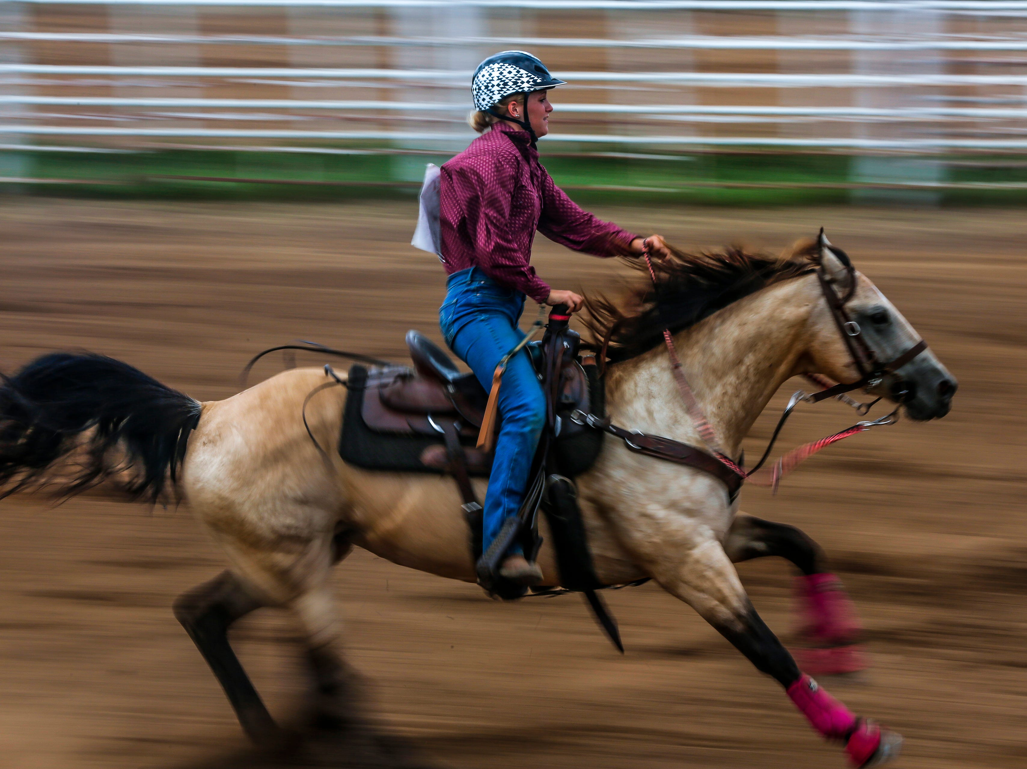 A rider competes in the barrel racing competition during the Amherst Little Britches Wisconsin Rodeo in Amherst, Wis., August 17, 2018.