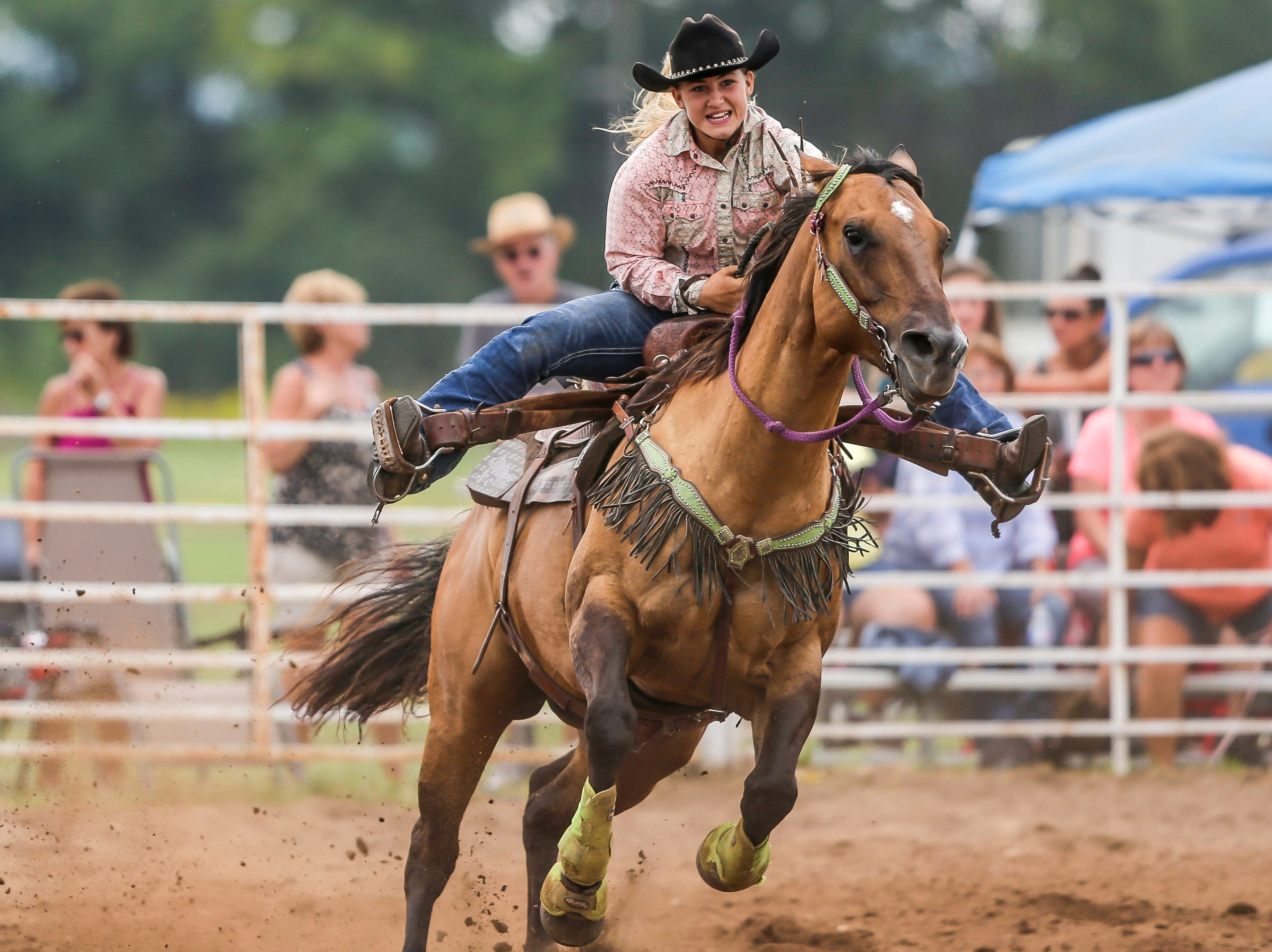 A competitor competes in the barrel race during the Amherst Little Britches Wisconsin Rodeo in Amherst, Wis., August 17, 2018.