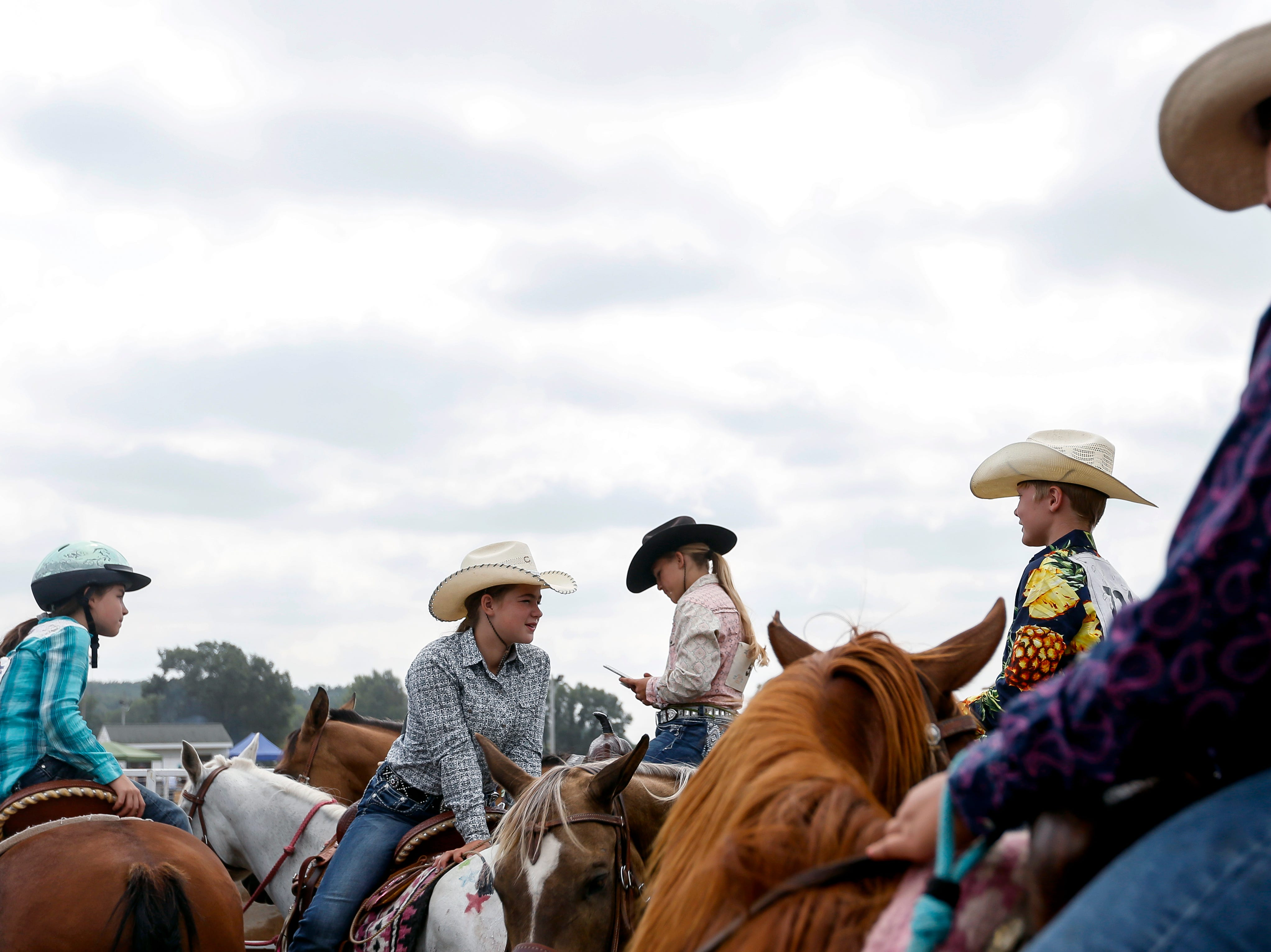 Competitors sit on their horses before competing in the Amherst Little Britches Wisconsin Rodeo in Amherst, Wis., August 17, 2018.