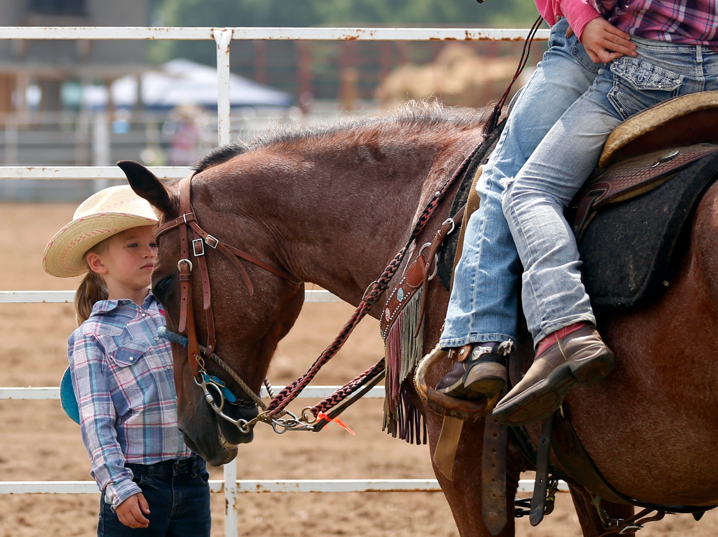 Girls hang out around a horse during the Amherst Little Britches Wisconsin Rodeo in Amherst, Wis., August 17, 2018.