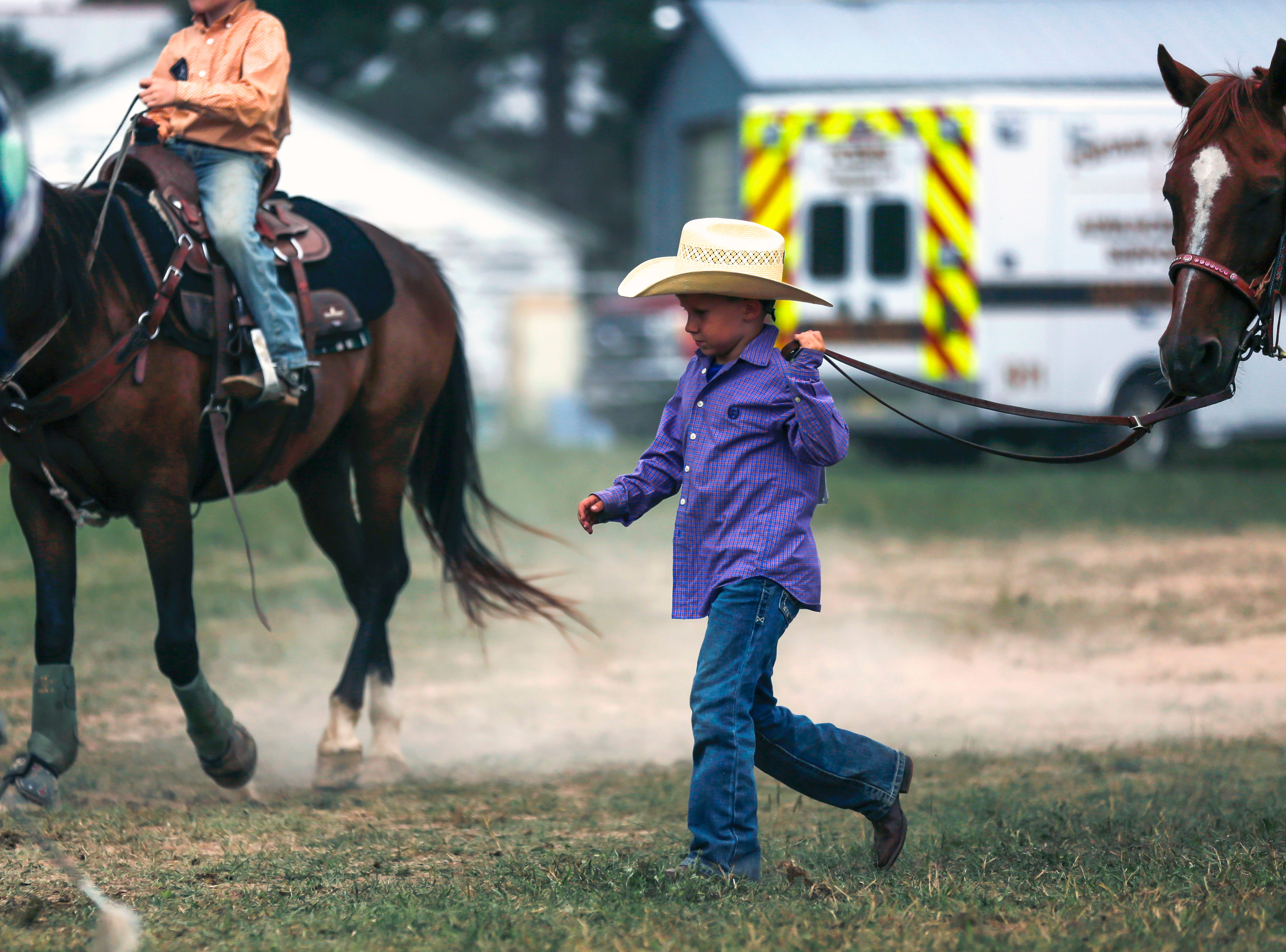 A boy leads his horse through the fairgrounds during the Amherst Little Britches Wisconsin Rodeo in Amherst, Wis., August 17, 2018.