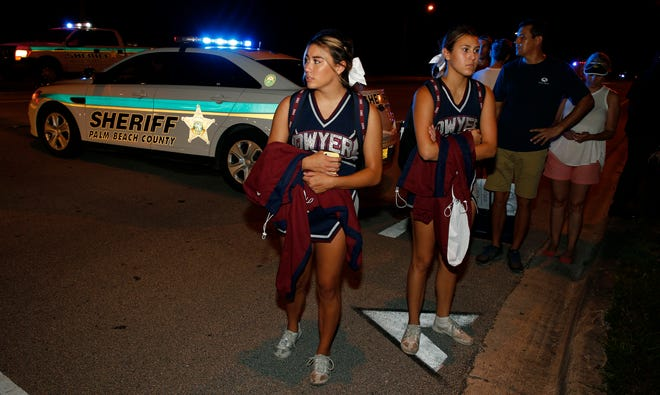 Dwyer High School cheerleaders walk past a roadblock following a shooting incident at a practice football game between Dwyer and Palm Beach Central High School, Friday, Aug. 17, 2018, in Wellington, Fla. A high school football stadium was evacuated after gunshots rang out Friday night in what authorities say stemmed from an altercation between students. (AP Photo/Joe Skipper)