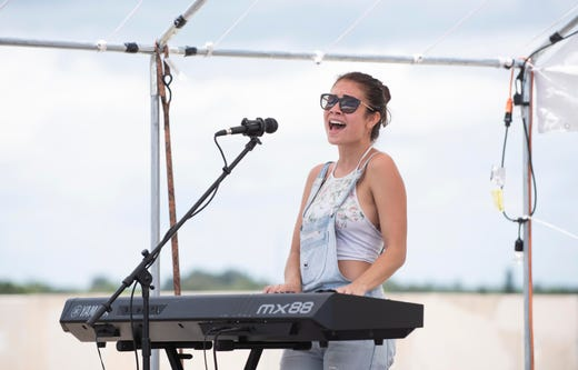 """""""You can go play somewhere where there's already a scene, but I think it's cooler to build a scene and be part of something up and coming and unique,"""" said Summer Gill, of Stuart, who plays during the Snorkel Corn Summer Classic on Sunday, August 19, 2018, on top of the Orange Avenue parking garage in downtown Fort Pierce. This was the first year for the event which featured a live music showcase with 16 acoustic acts and food and art vendors. Visitors were encouraged to bring a musical instrument to donate to the Bluebird Educational Foundation, which provides musical instruments to students in the St. Lucie County school system."""