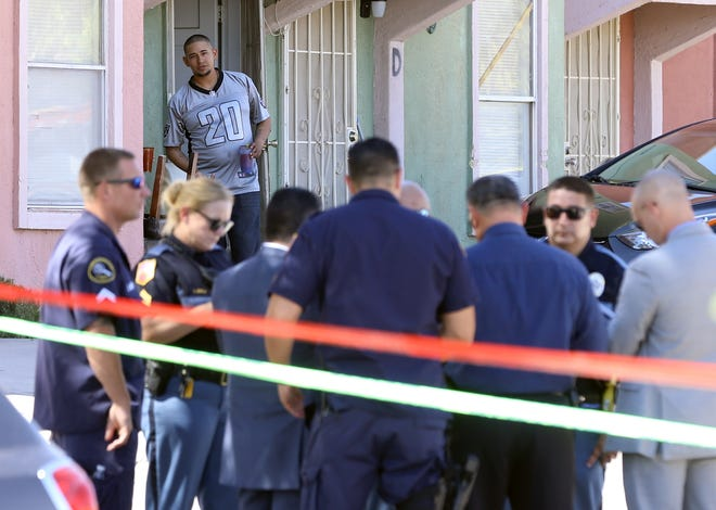A resident peeks out of his home as police investigate a homicide Sunday at the 10700 block of Forest Ridge Lane in East El Paso.