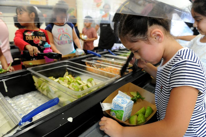 Mia Martinez puts vegetables on her lunch plate at Driffill School in Oxnard. The Oxnard School District offers free breakfast and lunch to the entire school population.
