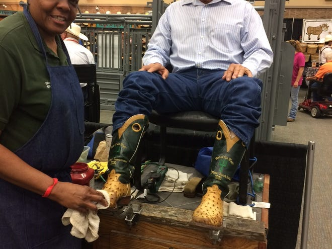 James Gholson, former foreman of the Pitchfork Ranch, getting his boots shinned by Trinita Stevenson in the Olsen- Stelzer booth at the Texas Ranch Rodeo in Wichita Falls.