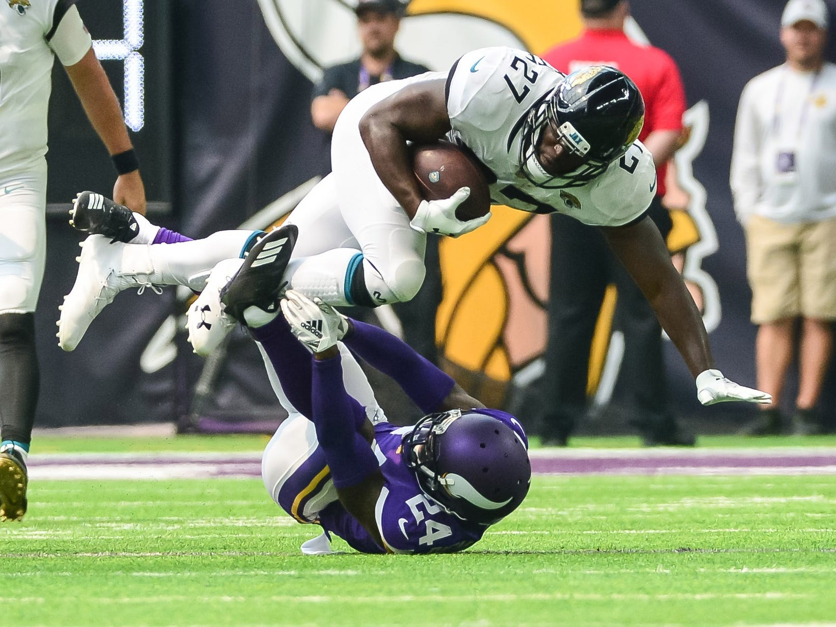 Jaguars running back Leonard Fournette (27) gets tripped up by Vikings cornerback Horace Richardson (24) during the second quarter.