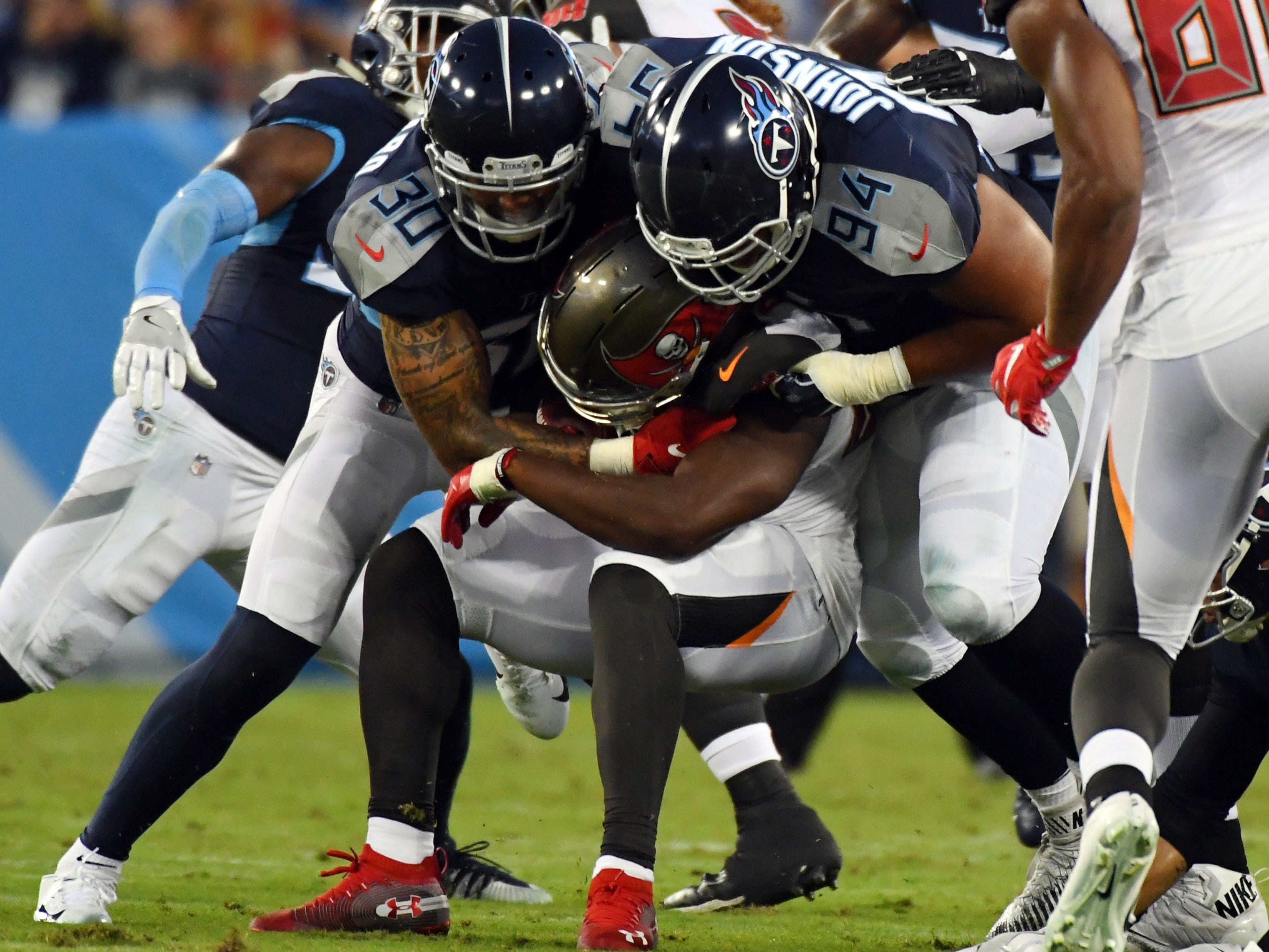 Buccaneers running back Peyton Barber (25) gets stuffed by Titans defenders Kenny Vaccaro (30) and Austin Johnson (94) during the first half at Nissan Stadium.