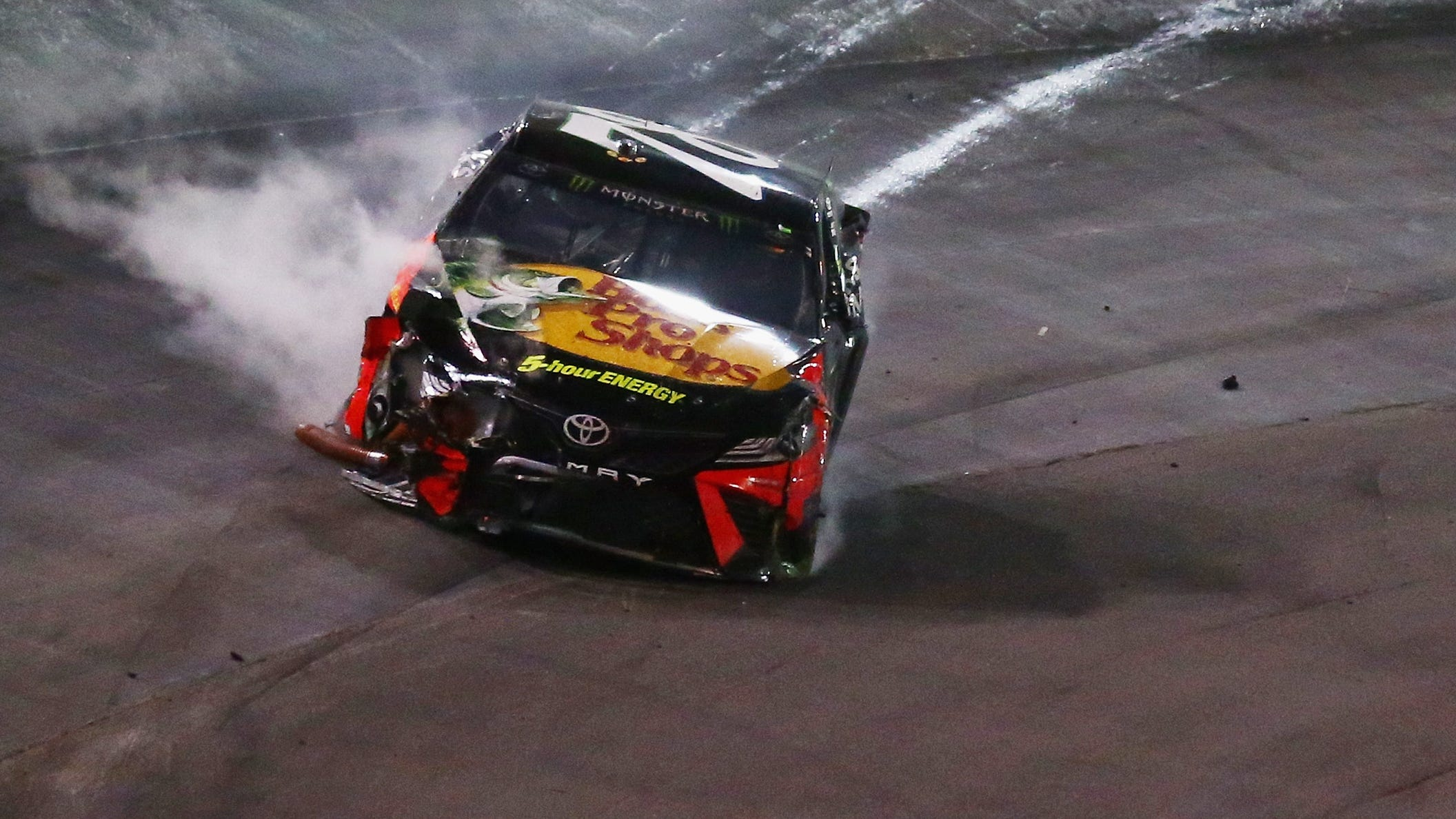 Martin Truex Jr. comes off the wall after being bumped by Kyle Busch during the Bass Pro Shops NRA Night Race.