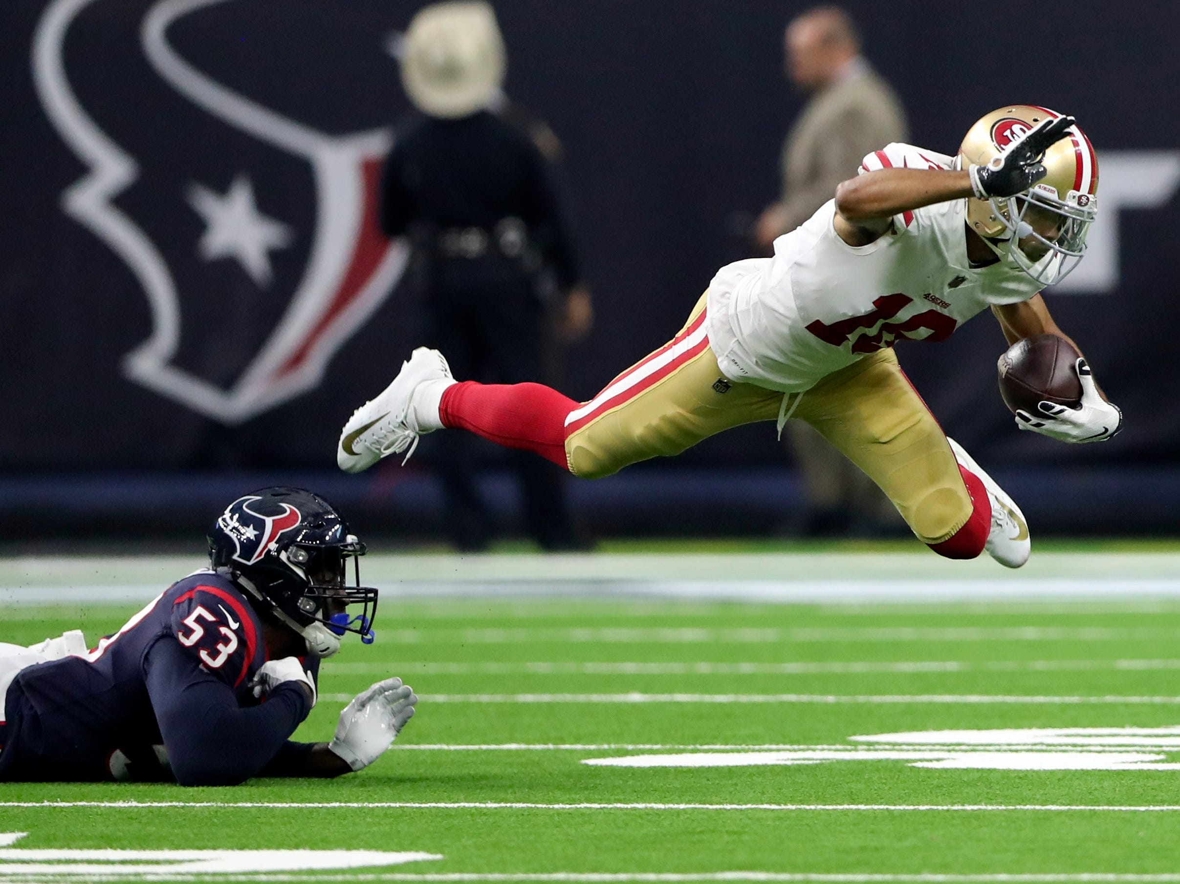 49ers wide receiver Dante Pettis (18) gets tripped up by Texans linebacker Duke Ejiofor (53) during the first quarter.