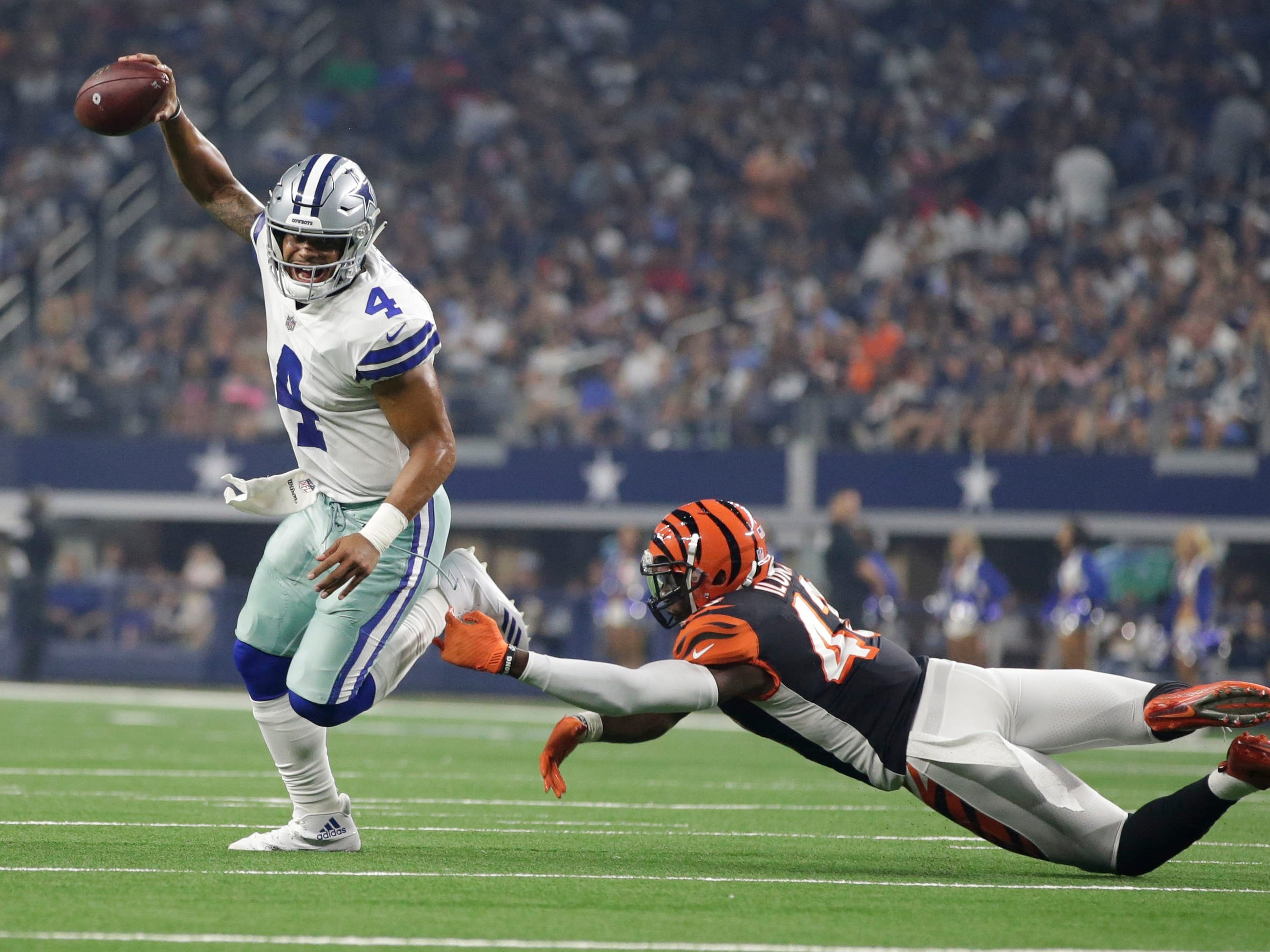 Cowboys quarterback Dak Prescott (4) eludes Bengals defensive back George Iloka (43) during the second quarter.