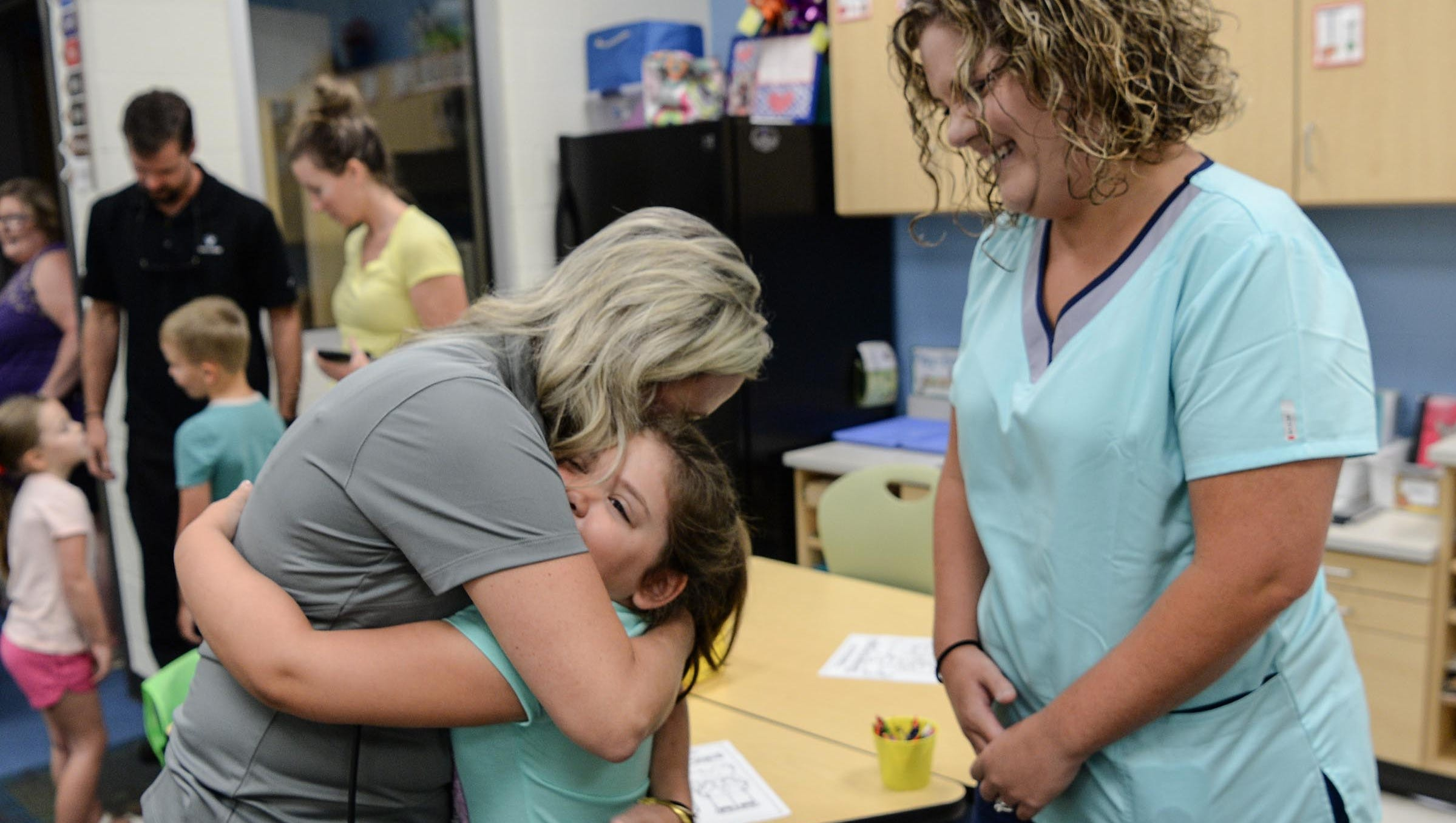 Caroline Zion, kindergarten teacher, hugs Caroline Smith near her mother Sarah Smith, right, during the opening hour of the first day of school at North Pointe Elementary in Anderson on Monday.