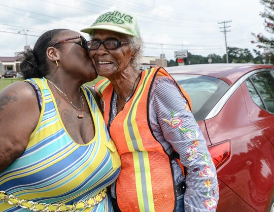 Neva Williams, left, of Anderson kisses her grandmother Estella Williams, before directing traffic in front of Westside High School in Anderson on Monday. Williams, who recently visited New York and was on the Today show, has been a crossing guard for 27 years.