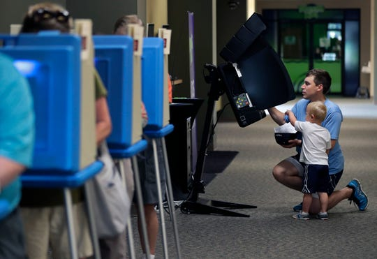 Paul Stevens votes with his son Walter, 3, Aug. 14, 2018,  at Pathways Church in Appleton. The field for the Kimberly Area School District Board of Education will narrow from seven candidates to six in a primary election held on Feb. 18.