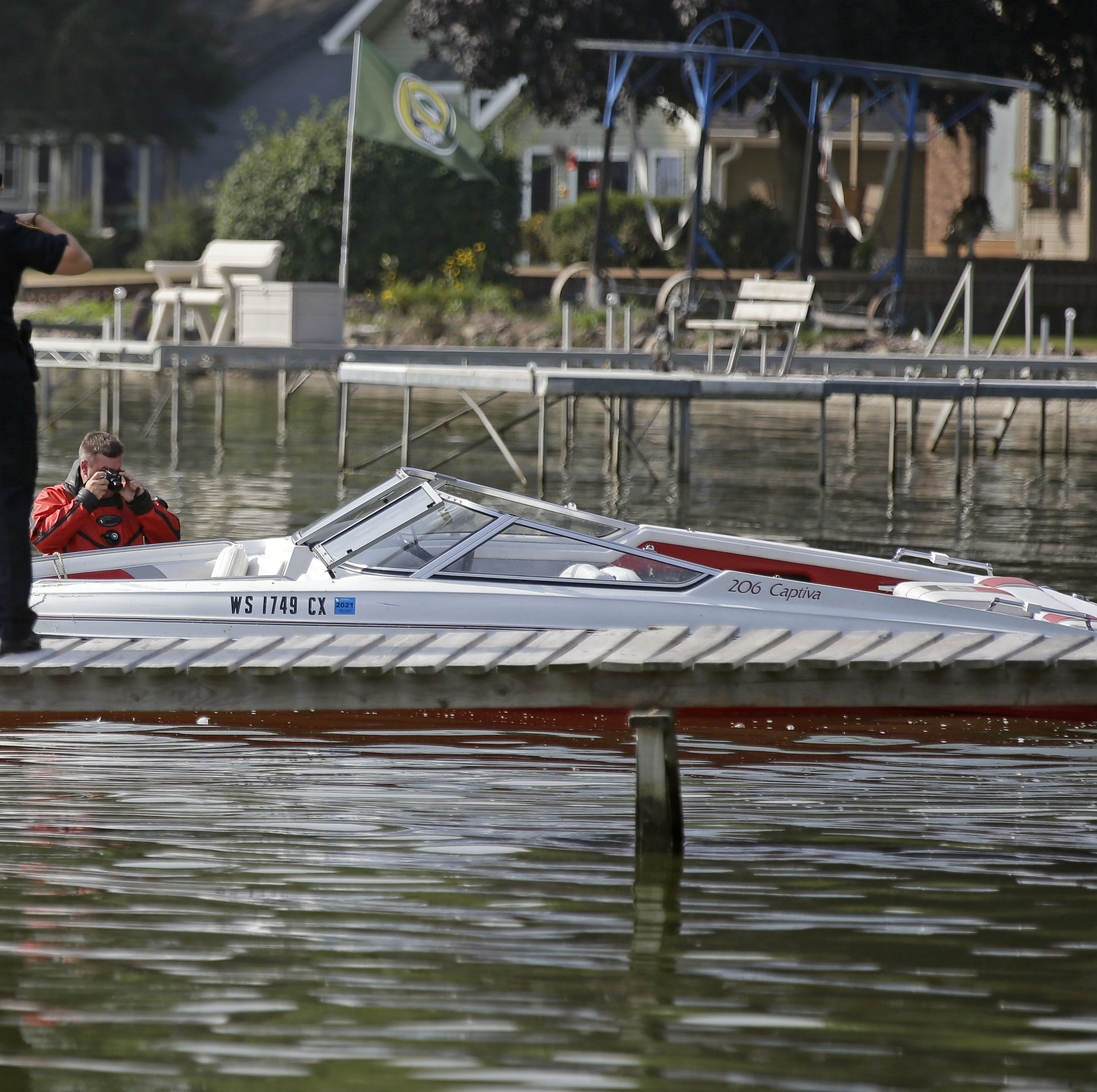 Jason Rippl, a member of the Winnebago County Sheriff's Department Rescue and Recovery Dive Team photographs a 20-foot Rinker Captiva boat before it is removed from Lake Winnebago Sunday near Vinland following a collision with another boat Saturday evening about a mile east of Paynes Point.