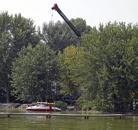 Jason Rippl, right, a member of the Winnebago County Sheriff's Department Rescue and Recovery Dive Team and Don Herman help remove a 20-foot Rinker Captiva boat from Lake Winnebago Sunday near Vinland following a collision with another boat Saturday evening about a mile east of Paynes Point.