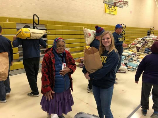 Macy McMillon, Cooper Student Council recording secretary the 2017-18 school years, carries groceries for a Navajo woman in Chinle, Arizona.