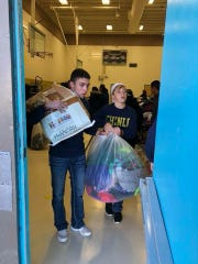 Andrew Benson, left, a senior last year, and sophomore representative Brody Stanford carry animal feed and clothing in Chinle, Arizona, where the Cooper High School Student Council serves each January.