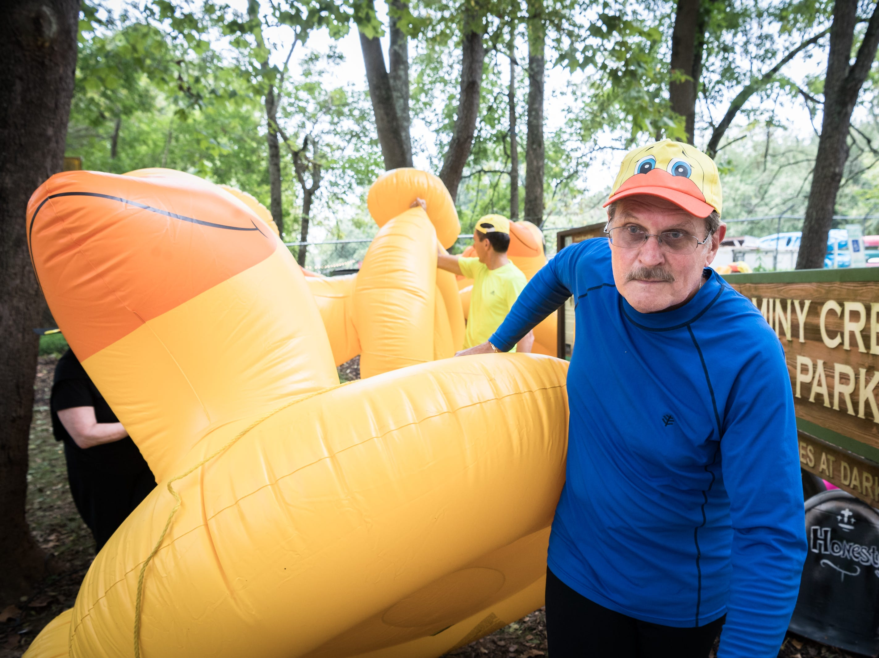 """John Ward, of the """"Just Ducky"""" Anything that Floats parade team, helps carry one of several duck flotation devices to put in to the French Broad River at Hominy Creek River Park, Saturday, August 18, 2018. The parade ended at New Belgium Brewery where RiverLink's RiverFest took place."""