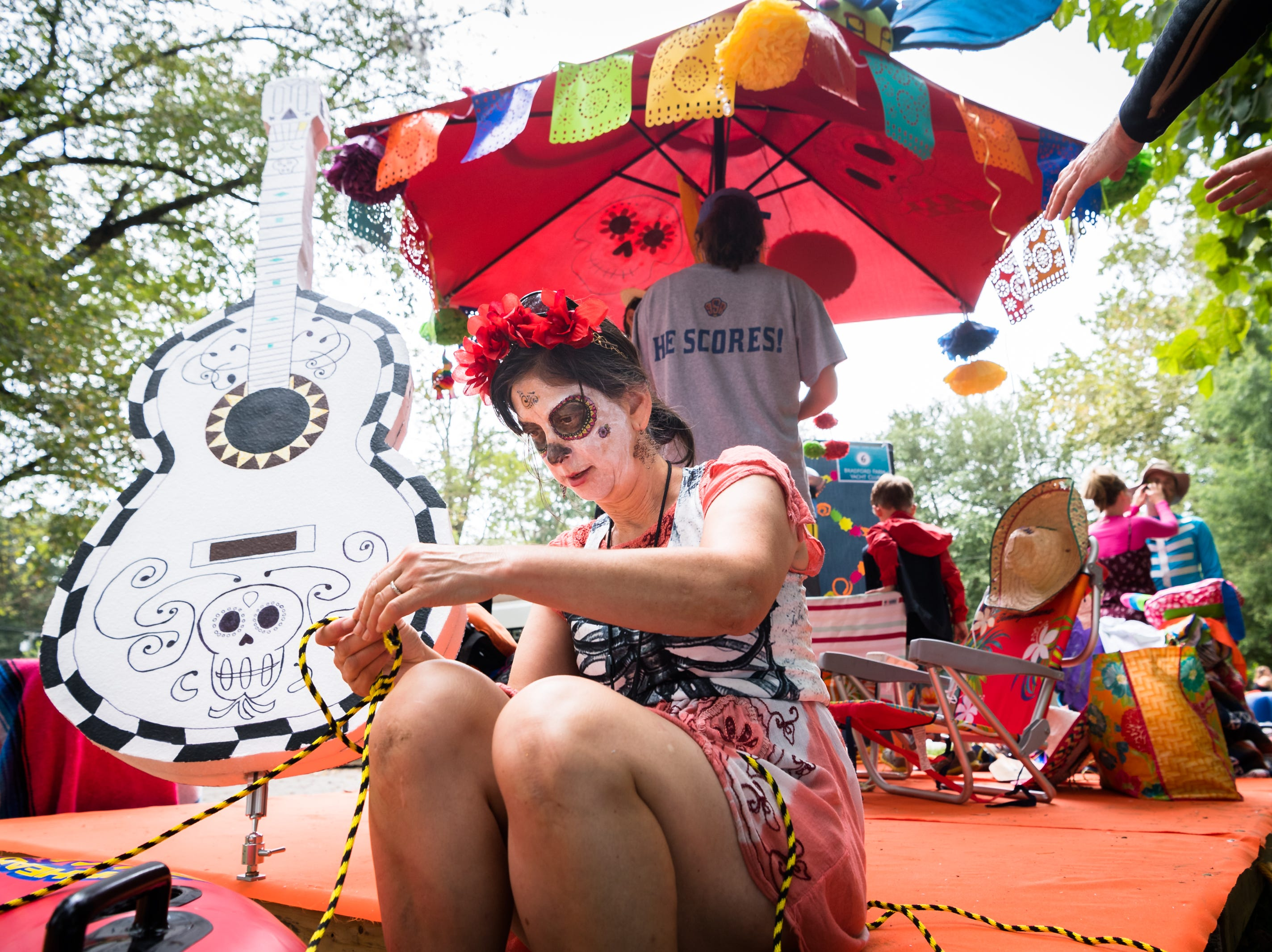 Susie Andrews of the Bradford Farm Yacht Club Anything that Floats team, helps in assembling their float before putting in to the French Broad River at Hominy Creek River Park, Saturday, August 18, 2018. The theme of the team's float was a Day of the Dead scene from the Disney movie Coco. The parade ended at New Belgium Brewery where RiverLink's RiverFest took place.