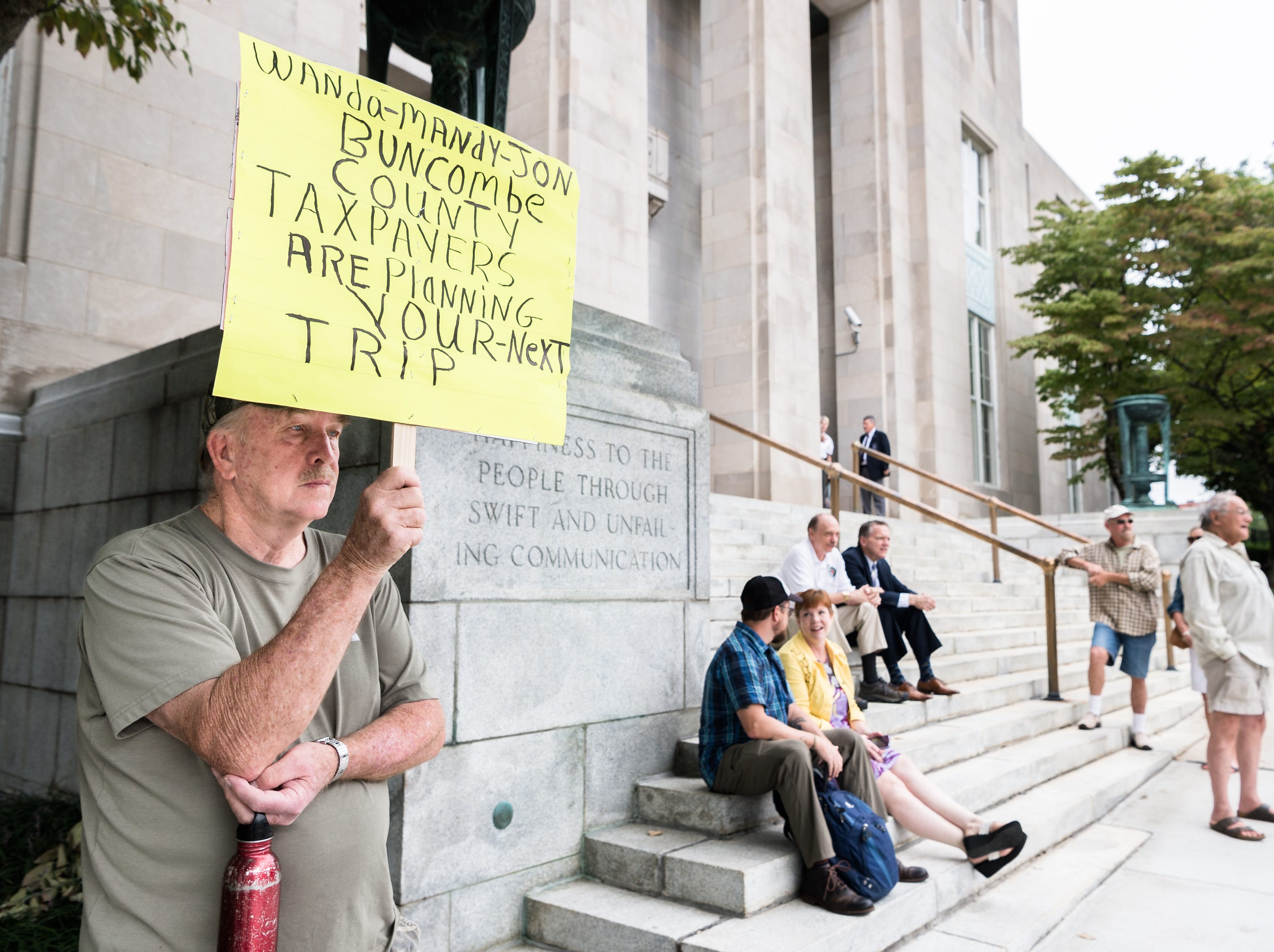 John Payne, local resident, stands outside the federal courthouse Monday, August 20, 2018, waiting for Jon Creighton, Mandy Stone and Wanda Greene, former Buncombe County administrators who have been indicted on 29 counts of wire fraud, one count of conspiracy to defraud the federal government, one count of receipt of bribes and kickbacks,  and one count of federal program fraud. Greene additionally was charged with six counts of tax fraud in connection to a life insurance scheme and embezzlement alleged by prosecutors in previous indictments.