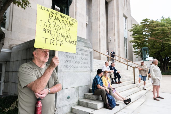 Weaverville resident John Payne stands out the federal courthouse Aug. 20, 2018, awaiting the arrival of three indicted Buncombe County officials. Ex-manager Wanda Greene and former assistant managers Mandy Stone and Jon Creighton are accused of engaging in a yearslong kickback scheme with Joe Wiseman, a Georgia-based engineer with North Carolina ties.