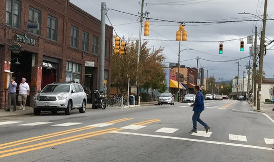 A pedestrian crosses Haywood Road in a marked crosswalk in October 2017. The West Asheville area continues to be a hot real estate market with some buyers suggesting the area's many bars and restaurants were a factor in purchasing there.