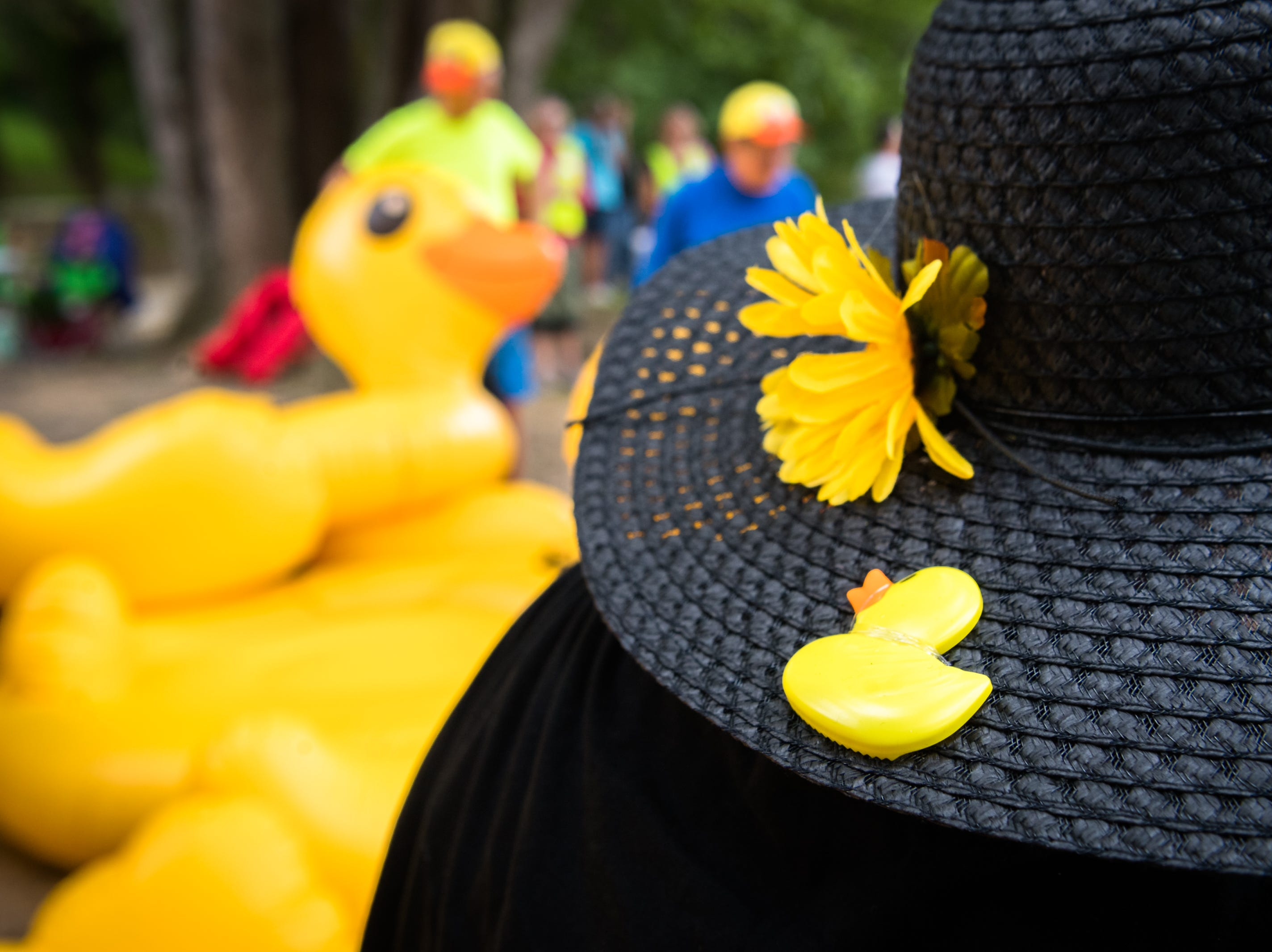One of the team members from the Just Ducky Anything that Floats parade team, sports a yellow duck pin on her hat as she waits to put in to the French Broad River at Hominy Creek River Park, Saturday, August 18, 2018. The parade ended at New Belgium Brewery where RiverLink's RiverFest took place.