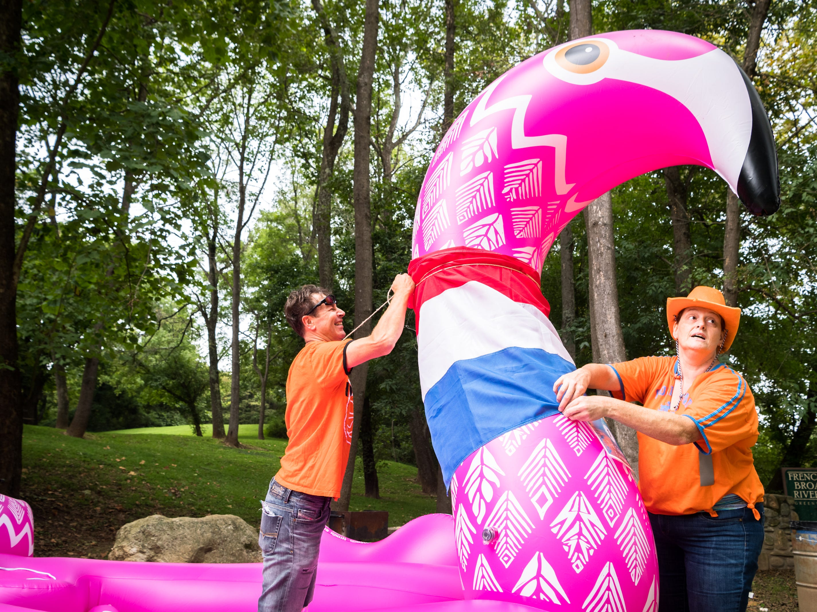 Marco Rozenbroek and Martine Rozenbroek, of Swannanoa, wrap the flag of the Netherlands around their giant flamingo raft before putting in to the French Broad River at Hominy Creek River Park as part of the Anything that Floats parade Saturday, August 18, 2018.