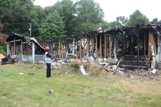 Battle Creek Fire Marshal Quincy Jones photographs the fire damage.