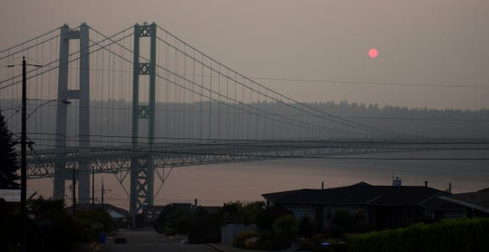 Smoke obscures the sun as it sets behind the Tacoma Narrows Bridge on Sunday. Poor air quality will be common across parts of the Pacific Northwest this week as winds push smoke from surrounding wildfires into the region, forecasters and regulators said, and air quality alerts are in effect for much of Washington state through Wednesday.