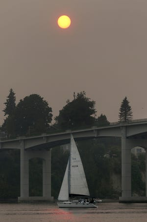 A sailboat passes the Manette Bridge in Bremerton on a hazy Sunday evening.