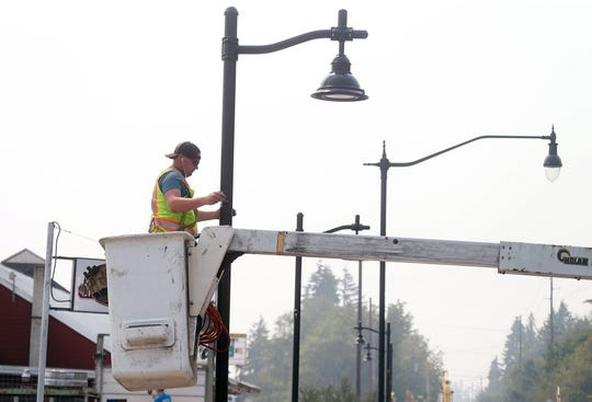 Ben Murphy, with Totem Electric of Tacoma, installs a new lamp post on Silverdale Way on Monday. Smoke from wldfires has been bothering him, but his job requires him to be outside.