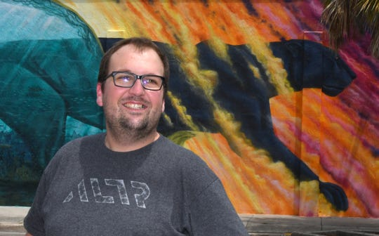 Chris Struttmann, founder, director of engineering, and chief architect of ALTR, stands in front of artist Christopher Maslow's Florida Tech panther mural in downtown Melbourne.