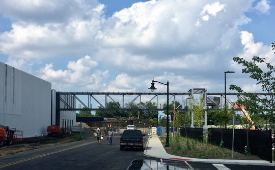 Construction workers leave the site of a pedestrian bridge at Subaru of America's new campus in Camden.