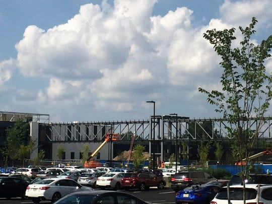 Construction workers are building a pedestrian bridge between two buildings on Subaru of America's Camden campus.