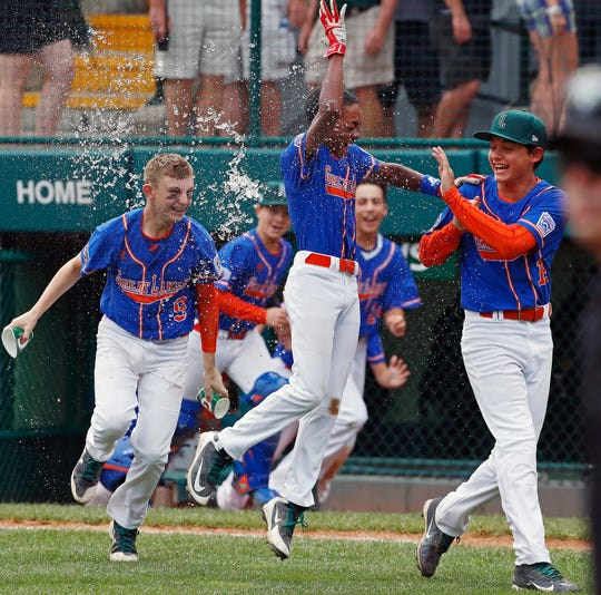 Grosse Pointe Woods, Michigan's Reggie Sharpe, center, gets a water bath from Cameron Schafer (9) as he begins to celebrate with Brennan Hill, right, after hitting a walk-off single in the bottom of the sixth inning of an elimination baseball game against Des Moines at the Little League World Series tournament in South Williamsport, Pa., on Monday. The Great Lakes champion defeated the Midwest winner 5-4.