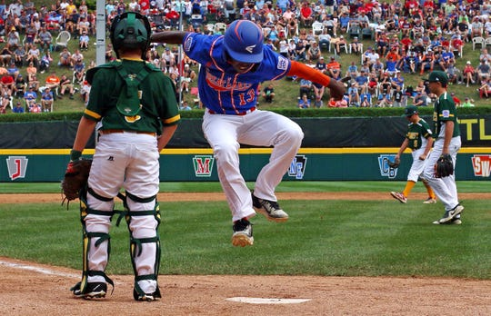 Grosse Pointe Woods-Shores' Oliver Service (13) leaps on home plate, past Des Moines, Iowa, catcher Kobe Kunert (5), scoring on a walk off single by Michigan's Reggie Sharpe off Des Moines pitcher Connor Duong in the bottom of the sixth inning of Woods-Shores' 5-4 win in an elimination baseball game in United States pool play at the Little League World Series tournament in South Williamsport, Pa., Monday, Aug. 20, 2018.