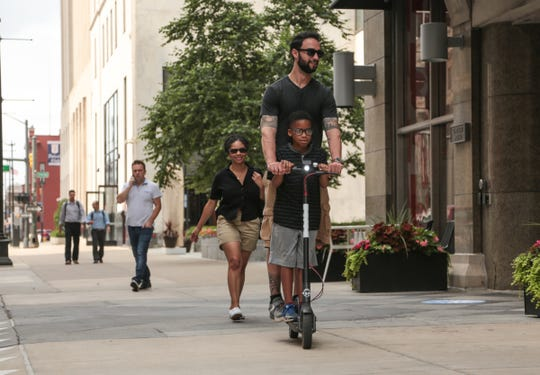 Adrienne Belford of Philadelphia follows along as her boyfriend Costantino Spinosa of Philadelphia rides with her son Jack Glenn on a rented Bird electric scooter near Campus Martius in downtown Detroit on Monday, August 20, 2018 while ending their trip to Detroit.