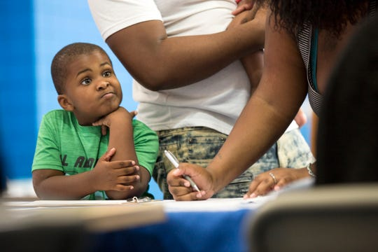 Jaylen Johnson, 4 of Detroit, signs up for the school year with his parents at Mackenzie Elementary/Middle School in Detroit, Mi., Wednesday, August 8, 2018.