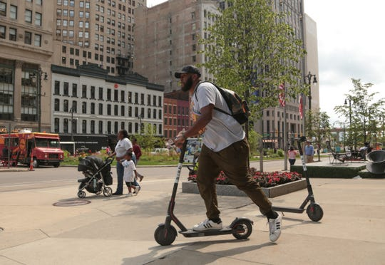Cj Edwards of Detroit rents a Bird electric scooter near Campus Martius in downtown Detroit on Monday, August 20, 2018 to leave for lunch.